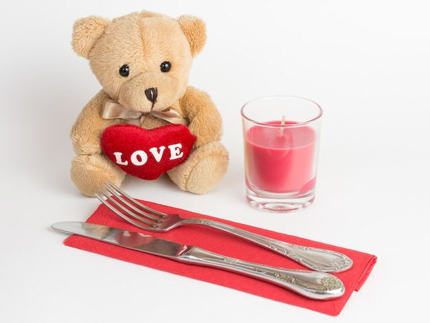 Teddy bear, candle and cutlery for valentines day