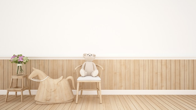 Teddy bear on chair and rocking horse in kid room or nursery