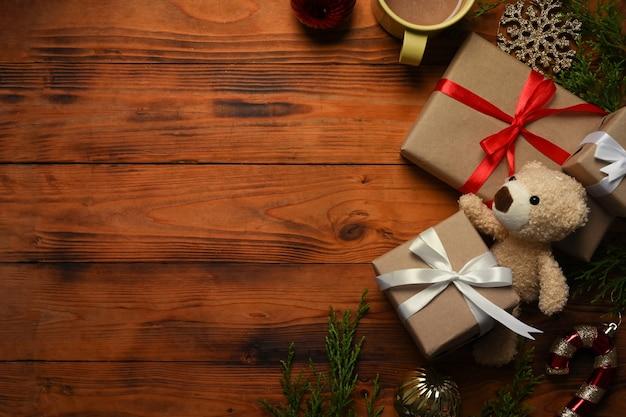 テディベア、クリスマスプレゼント、ホットコーヒー、木製のテーブルにモミの木の枝。クリスマスと新年のコンセプト。