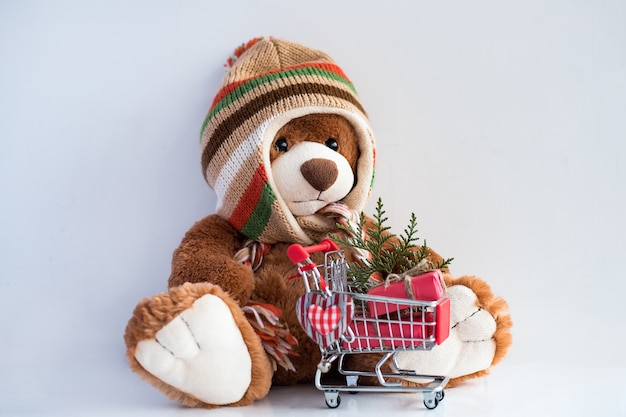 Teddy bear and christmas gifts in supermarket trolley on white