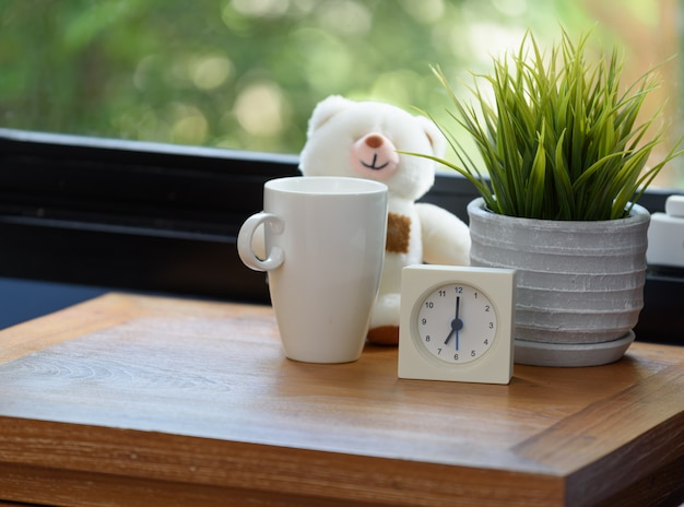 A teddy bear,coffee cup and white alarm on wood table in blue bedroom