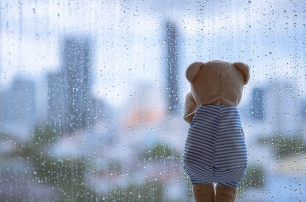 Teddy bear crying alone at window when raining with blurred city