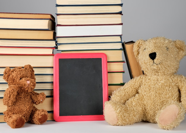 Teddy bear and empty black board in red frame on pile of books