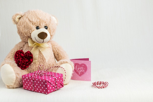 Teddy bear, gift box, greeting card and heart on a light textured background
