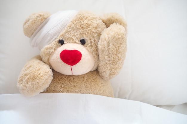 The teddy bear has gauze on the head