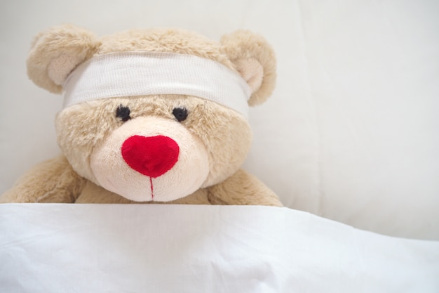 The teddy bear has gauze on the head