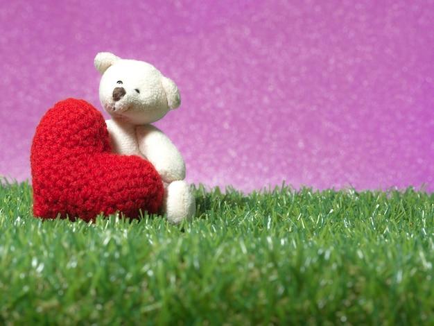 Teddy bear holding a handmade red heart on green grass background