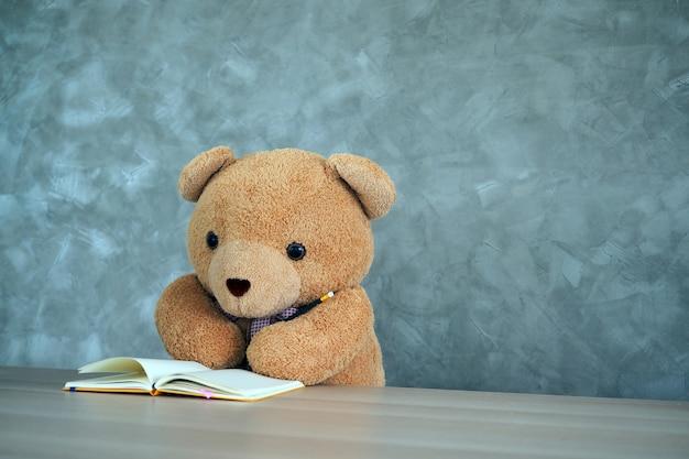 Teddy bear holding a pencil reading a book.