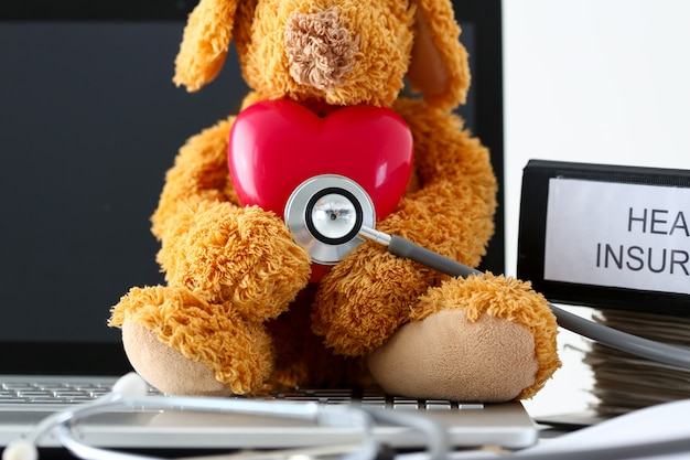 Teddy bear holding toy red heart listening with phonendoscope head