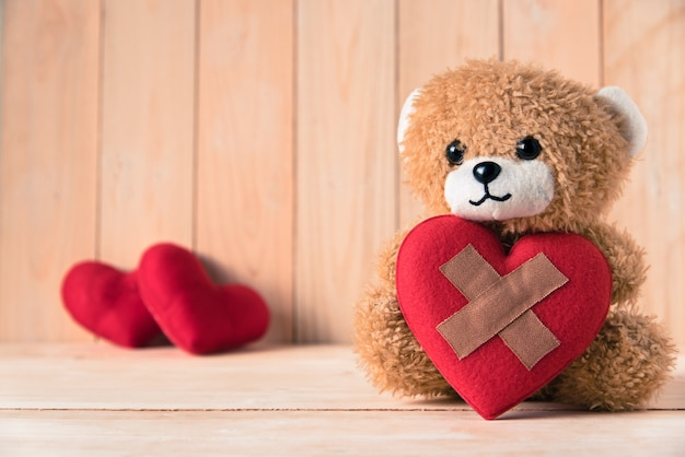 Teddy bear holding wound heart with couple red heart background