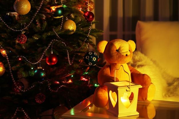 飾られたクリスマスツリーの背景に家のインテリアのテディベア