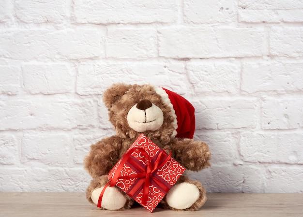 Плюшевый мишка в шляпе санта-клауса и коробке, перевязанной красной лентой