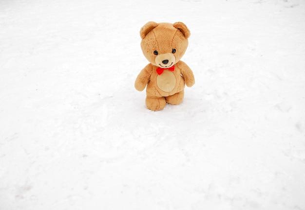Плюшевый мишка зимой. зимняя концепция. бурый плюшевый мишка с бабочкой на шее идет по белому снегу, зимний день. игрушка снаружи