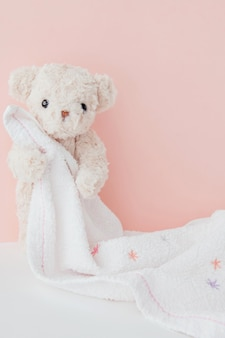 Teddy bear is hugging towel with pink pastel background,cute teddy bear covered towel after bath
