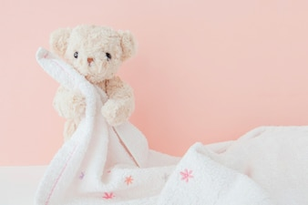 Teddy bear is hugging towel with pink pastel background