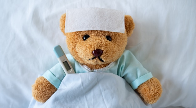 The teddy bear is sick on the bed with a high fever. there is a fever reducing sheet on the forehead.