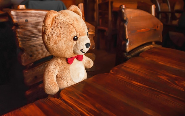 테디 베어는 테이블에 앉아 있습니다. 목재 가구와 갈색 곰 장난감. 동화 에피소드. 붉은 나비.