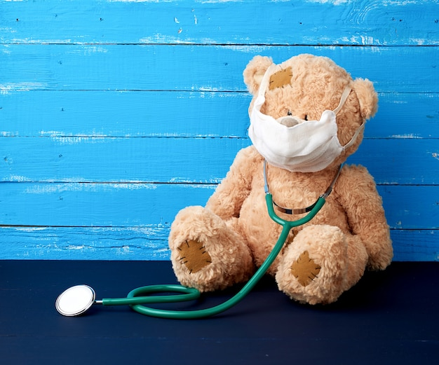 Teddy bear is sitting in a white medical mask and a green stethoscope is hanging on his neck