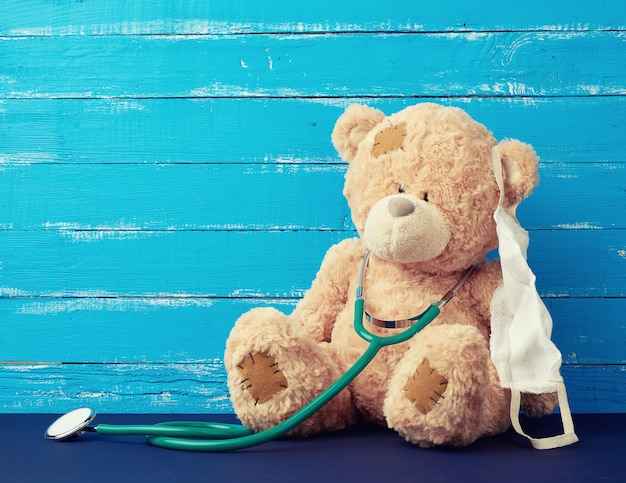 Teddy bear is sitting in a white medical mask with green stethoscope hanging on his neck