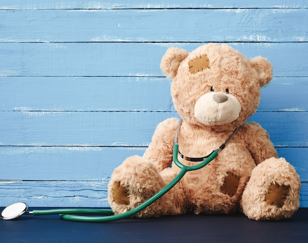 Teddy bear is sitting with green stethoscope hanging on his neck
