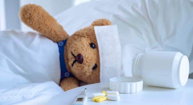 Teddy bear lies on the be next to medicines