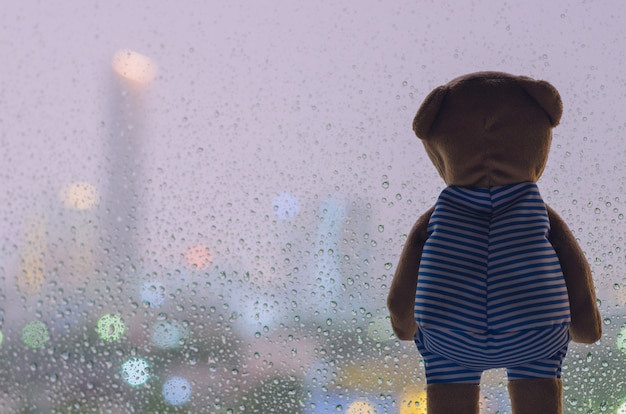 Teddy bear looking out from glass window when raining at night.