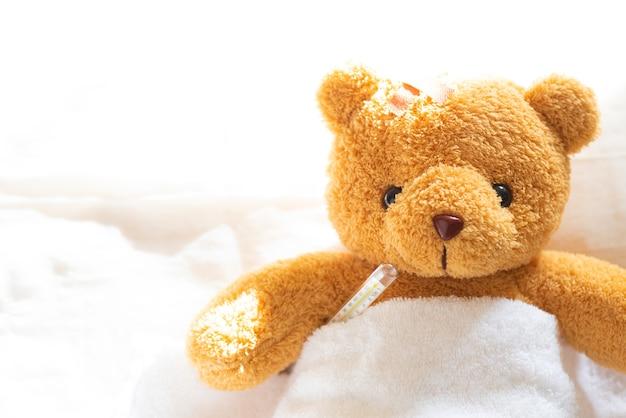 Плюшевый медведь, больной в больничной койке с термометром и штукатуркой.
