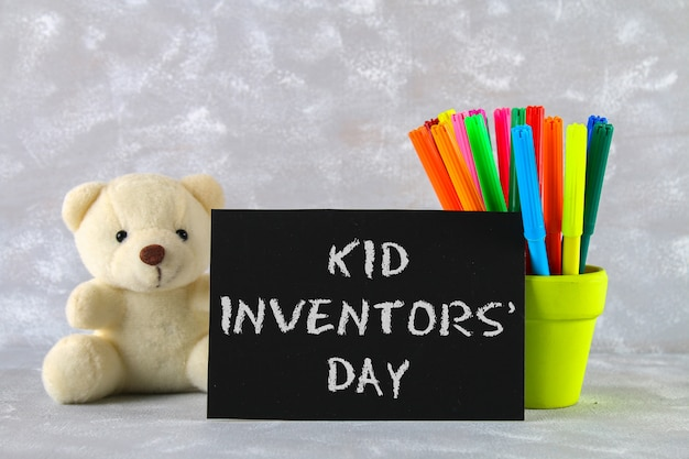 Teddy bear, markers, plaqu on a gray background. text - kid inventors' day.