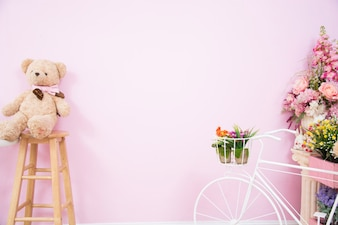 Teddy bear on a wooden chair with flowers and a white bicycle with pink walls.