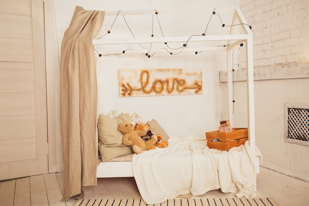 Плюшевый мишка на деревянной кровати в интерьере спальни белого ребенка.