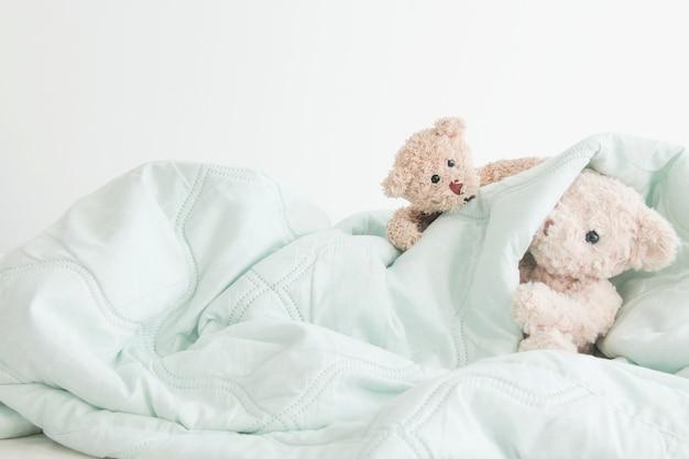 Teddy bear playful in white blanket