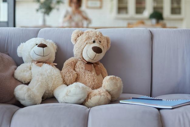 自宅で勉強するためのノートと一緒にソファに座っているテディベアのぬいぐるみ