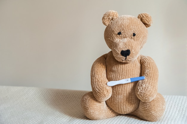 Teddy bear and positive pregnancy test close up  children's toy bear, booties, test.