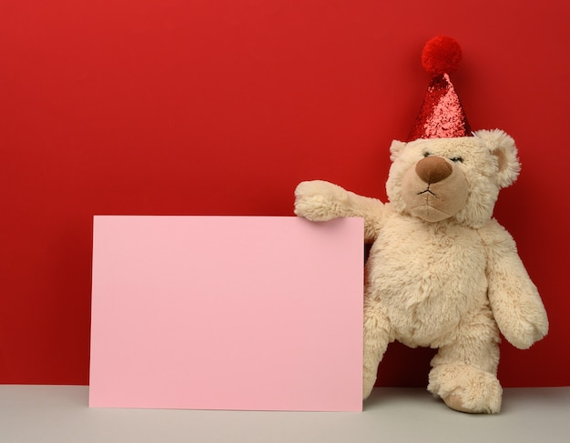 Teddy bear in a red festive hat holds a pink sheet of paper, copy space