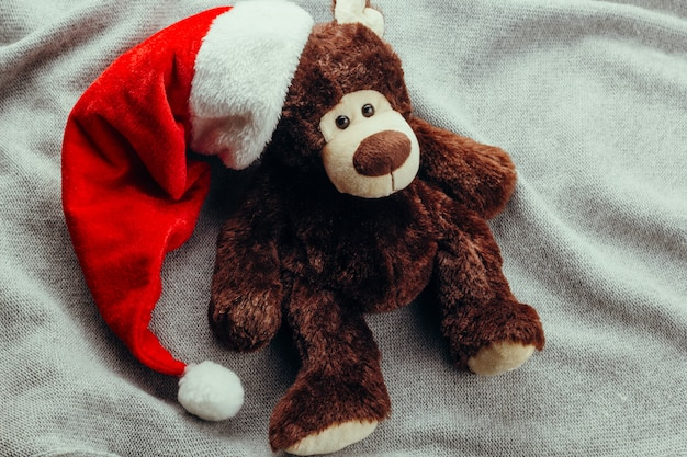 Teddy bear in santa claus cap on a knitted background
