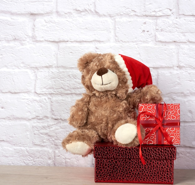 Teddy bear in santa claus hat and box tied with red ribbon