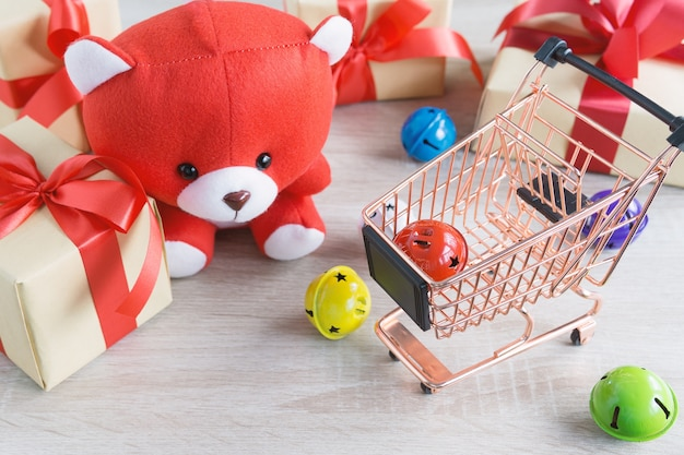 Teddy bear and shopping cart with christmas gifts box  red ribbon and colorful bell