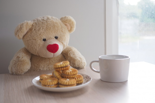 Teddy bear sit drinking cocoa and cookies on the table.