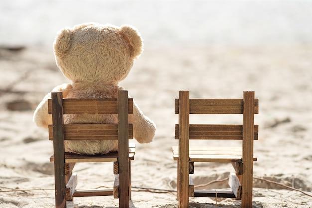 テディベアは海の景色を望む木製の椅子に座っています。愛と関係の概念。夏の美しい白い砂浜。