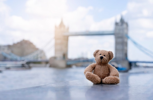 Teddy bear sitting alone with blurry london tower bridge background