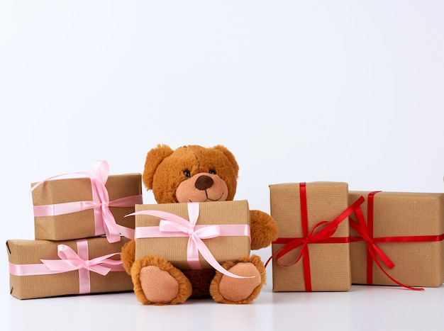 Teddy bear and  stack of gifts in boxes wrapped in brown paper