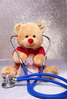 Teddy bear and stethoscope on white