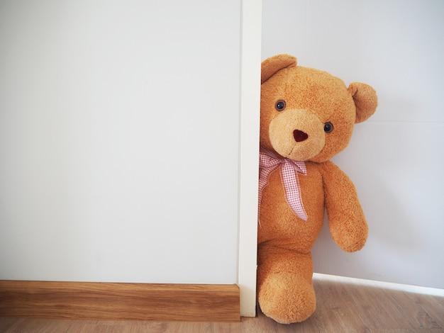 The teddy bear stood secretly behind the wall.