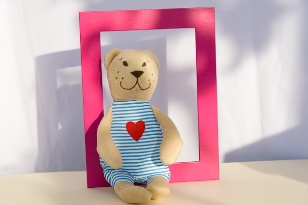 Teddy bear stuffed toy sits on shelf in pinhk frame. copy space, template