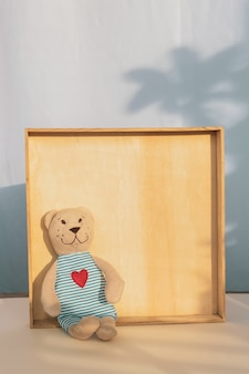 Teddy bear stuffed toy sits on shelf in wooden frame. shadow of palm. copy space, template
