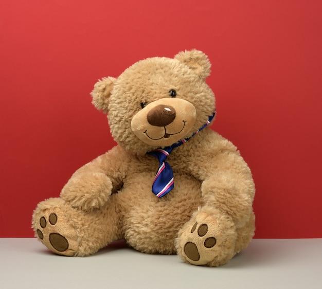 Teddy bear in a tie sits, children's toy
