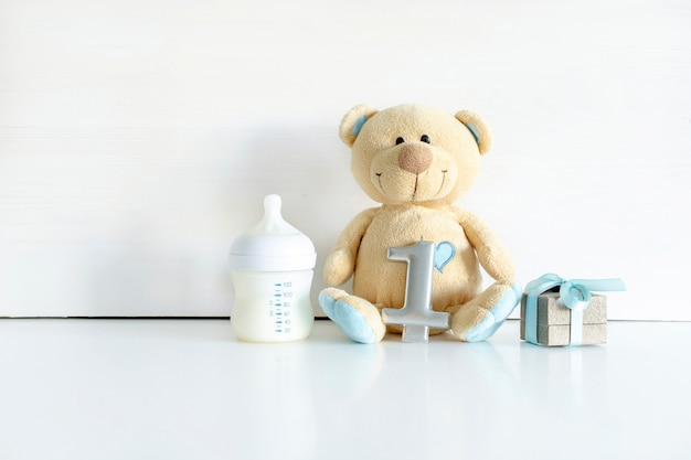Teddy bear toy, gift box, digit one on white table with copy space. baby shower, accessories, decorations, stuff, present for boy girl child first year happy birthday, first newborn party background