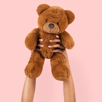 Teddy bear toy held by a hand for kids