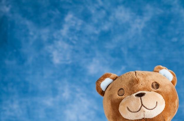 Игрушка плюшевый мишка на фоне голубого неба с copyspace
