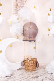 Teddy bear traveler and pilot. childhood dreams. stylish vintage children's room with aerostat, balloons, textile clouds and the moon. children's location for a photo shoot: aerostat, balloon, clouds